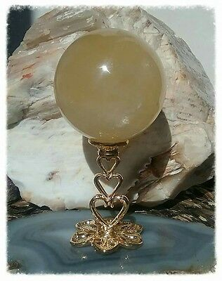 yellow calcite gemstone sphere with gold heart stand