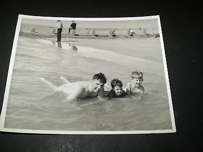 social history 1950's seaside dad and young boys laying in the sea photograph