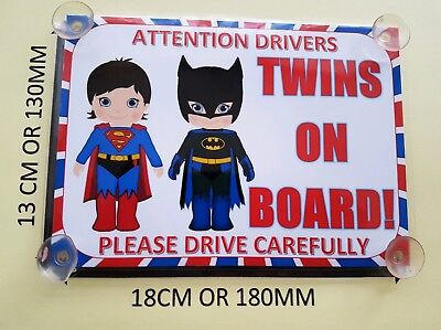 Twins Dressed As Batman And Superman twins On Board Car Laminated Sign