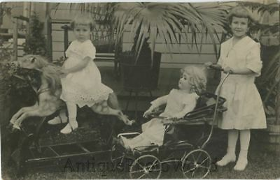Cute girls with toy rocking horse large doll in stroller antique toy rppc photo