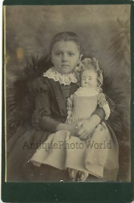 Beautiful girl holding a large doll antique toy cabinet photo