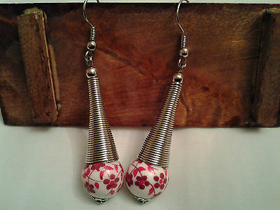 A pair of hand made earrings with alloy ring & porcelain bead with red flower
