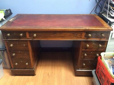 Antique writing desk, mahogany wood with red leather top.