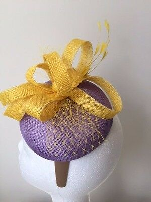 Purple fascinator with yellow loops, feathers and netting on a blonde headband!