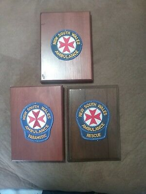 3 X New South Wales Ambulance Service Shoulder Patches. Mounted On Timber...