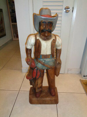 "Vintage Rare Hand Carved Wooden Cowboy Carrying Saddle Statue (35 by 13 by 8"")"
