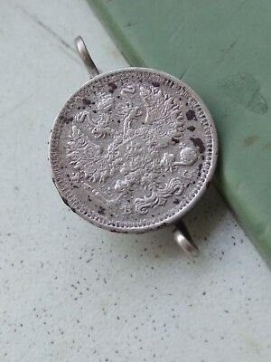 An antique silver earring from a coin of 10 kopecks in 1915. Russian empire