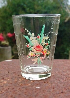 Vintage medicine measuring glass with hand painted flowers