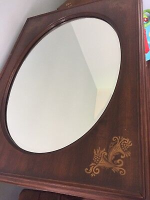 Hitchcock wood framed beveled oval mirror with gold corner accents.