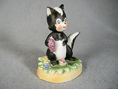 Cute Bisque SKUNK holding grapes on pedestal