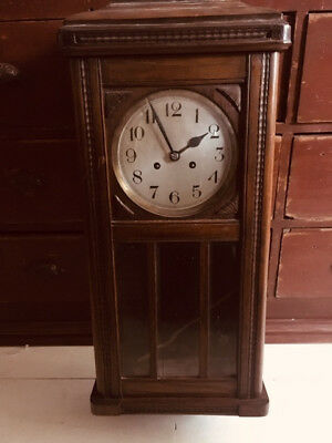 old wooden chiming pendulum wall clock, carved detail, panelled glass door