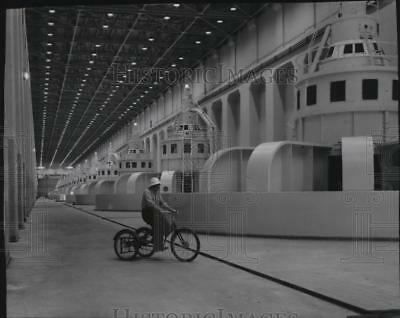 1957 Press Photo Generator operator riding a tricycle in McNary Dam powerhouse