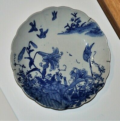 a blue and white antique oriental plates decorated with flowers and birds