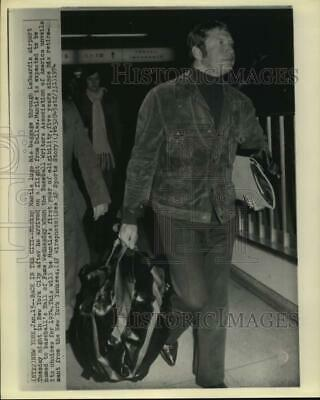 1974 Press Photo Mickey Mantle lugs baggage in LaGuardia airport, New York
