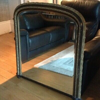 Large antique Victorian arched over mantle  mirror on bun feet.