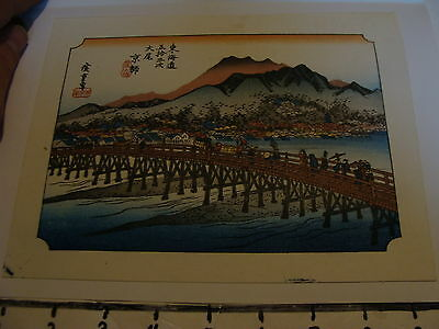 Vintage Japanese Woodblock Print: People traveling over bridge near village