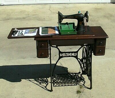 Antique Singer 66 treadle sewing machine with buttonholer, cabinet. Works good.