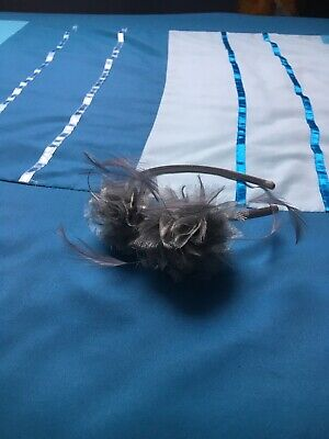 grey fascinator on a grey headband with grey flowers and feathers