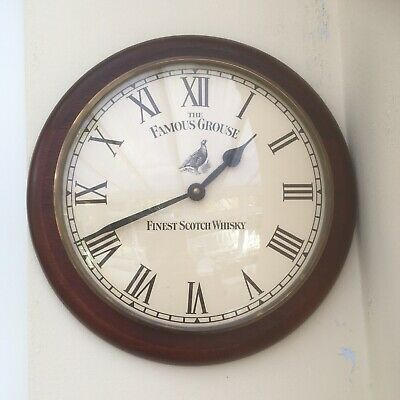 Famous Grouse whiskey clock in good condition, solid with mahogany surround