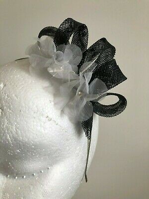 Black loop sinamay fascinator with white flowers on a silver headband.