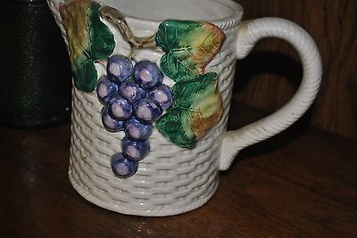 Decorative pitcher partially covered with grapes