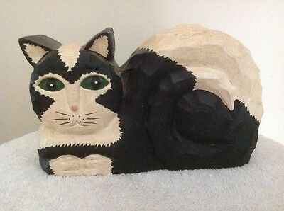 Cat carved wooden figurine, sitting.  Black and white.  Detailed workmanship.