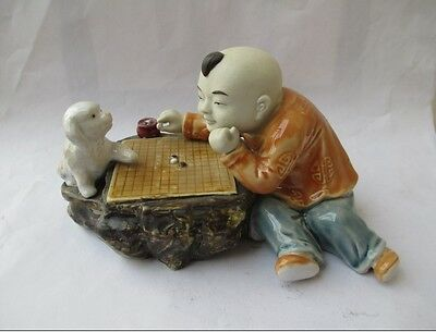 Antique ceramic statues chess players and small animal (dog)