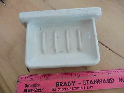 Vintage porcelain dish holder holds soap wall mounted next to shower tub