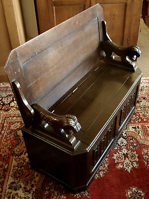 Reproduction Oak Monks bench with carved lion supports.