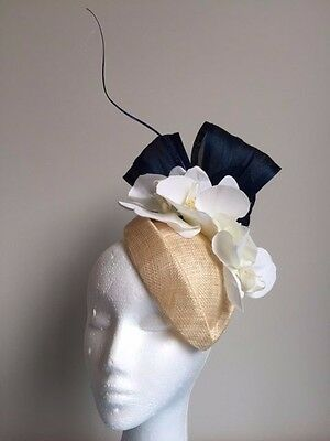 Cream air hostess fascinator with navy silk abaca loops and cream orchards.