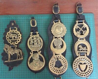 Vintage horse brasses in sets of 2 or 3 on leather straps. 10 in total