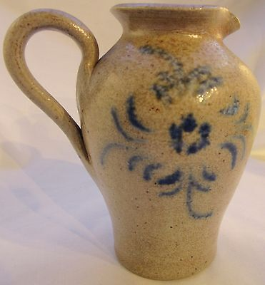 Small Rustic stoneware pottery pitcher featuring hand-painted design.