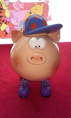 Piggy bank pig wearing hat and has spring legs