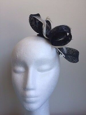 Navy blue sinamay loop fascinator with white feathers on a clear comb