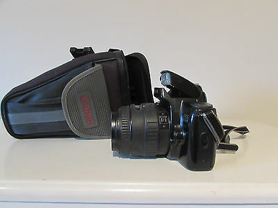 A vintage Canon EOS 1000F 35mm camera with additional lens and carry bag
