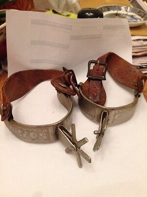 vintage western cowboy spurs with decorative design and leather straps