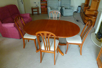 """Teak """"drop leaf"""" dining table, compact with 4 upholstered chairs."""
