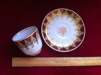 Gold and red tea cup and saucer.
