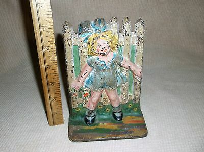 antique cast iron doorstop, girl w/ bow at fence, Shirley Temple?...