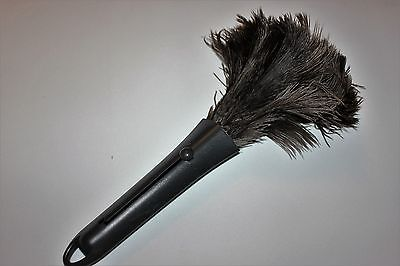 One compact  grey ostrich feather duster retractable in plastic case