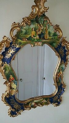 Vintage mirror framed in carved wood with Rococo style and old-world paintings
