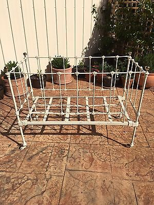 Decorative antique cast iron cot on casters. Brass knobs, solid grid base.