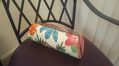 small handmade flower accented handbag with large clasp and satin interior