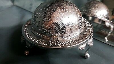 A  silver plated roll top butter/caviar dish with very ornate patterns.