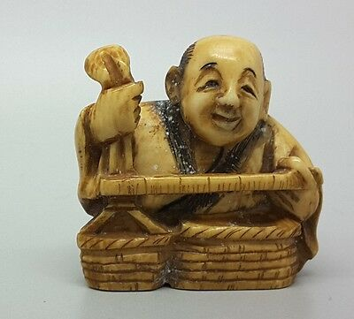 Meiji era Netsuke of a tradesman measuring, signed, Japanese