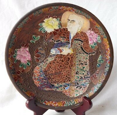 Japanese Relief Moulded Pottery Plate With Seated Figure With Scroll And Flowers