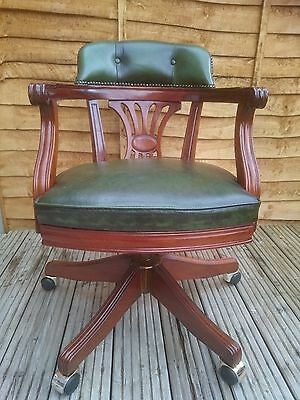 Antique 1960's green leather mahogany captain revolving office chair on casters.