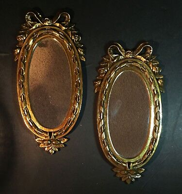 Pair of gold oval mirrors.  Hollywood Regency style. Small with bows on top.