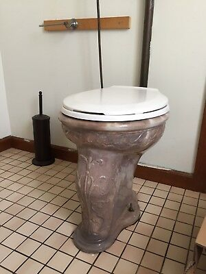 Antique toilet with wall hung tank.