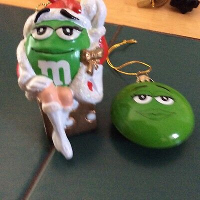 m&m 2 ornaments green girl sitting on dice all dressed up & green funny face